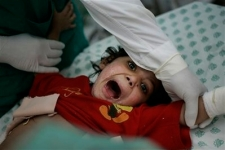 Rawan Abu Taber, 4, screams in pain as doctors change bandages to her severe burns, at the Shifa hospital in Gaza City, Wednesday Jan. 21.